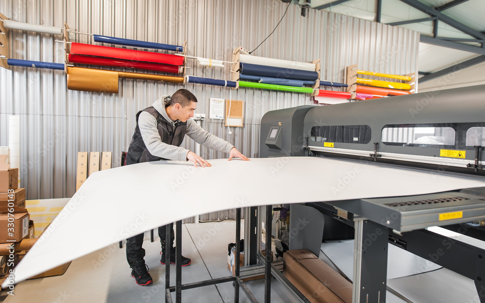 Fototapeta Technician operator works on large premium industrial printer plotter machine