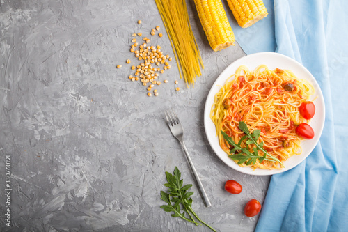 Corn noodles with tomato sauce and arugula on a gray concrete background Canvas Print