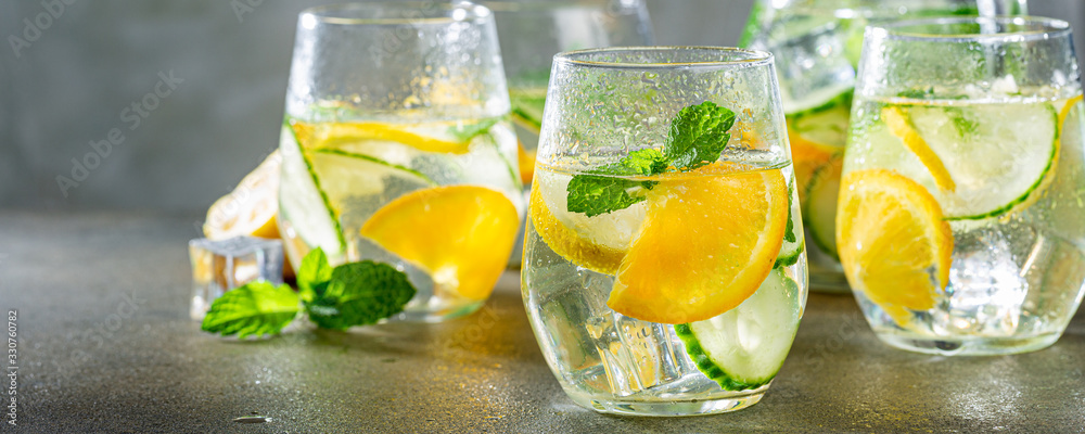Fototapeta Summer healthy lemonade, cocktails of citrus infused water or mojitos, with lime lemon orange, ice and mint, diet detox beverages, in glasses on gray background. Banner