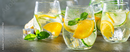 Fototapeta Summer healthy lemonade, cocktails of citrus infused water or mojitos, with lime lemon orange, ice and mint, diet detox beverages, in glasses on gray background. Banner obraz