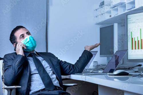 Fotografía Manager in abito si protegge con una mascherina e discute al celliulare seduto n