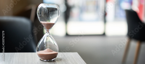 Hourglass on table office with copy space, Sand flowing through the bulb of Sandglass measuring the passing time. countdown, deadline, Life time and Retirement concept