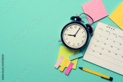 Fotografía close up of calendar and alarm clock on the green table background, planning for