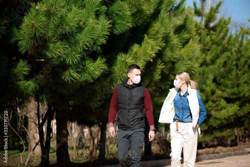 Obraz Young European man and woman in protective disposable medical mask walking outdoors afraid of dangerous NCoV 2019 influenza coronavirus mutated and spreading in China - fototapety do salonu