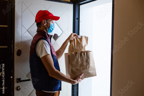 Fototapeta Delivery man holding paper bag with food on white background, food delivery man
