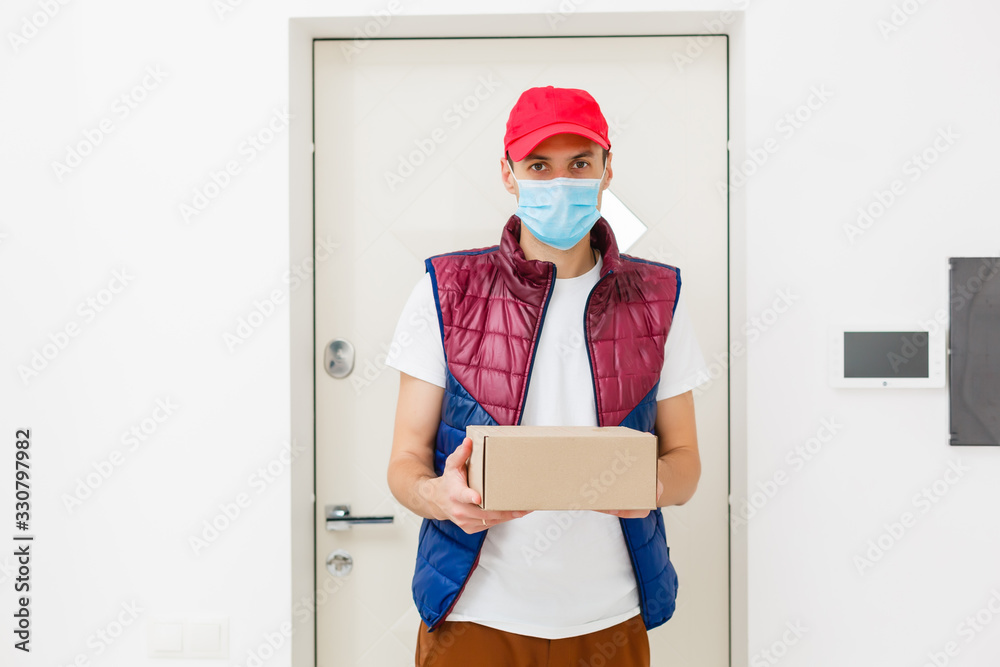 Fototapeta Delivery man holding paper bag with food on white background, food delivery man in protective mask