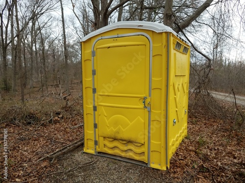 yellow portable toilet or outhouse with brown leaves