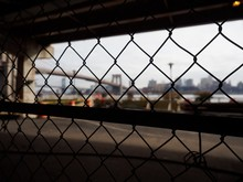 Looking Through A Fence Towards The Brooklyn Bridge, New York