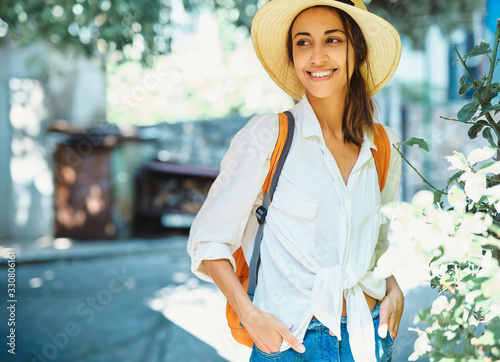 Fototapeta portrait happy carefree woman tourist in straw hat, white shirt walking and exploring small streets. obraz