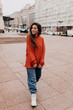 Attractive modern woman walking on the city street. Fashionable young woman in street in the city wearing orange pullover