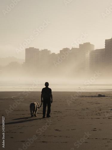 Photo Hombre paseando a su perro en soledad por una ciudad desierta en una mañana mist