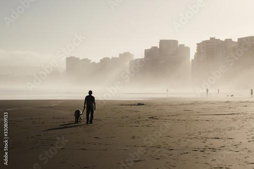 Hombre solitario pasando a su perro por la playa con edificios al fondo Wallpaper Mural