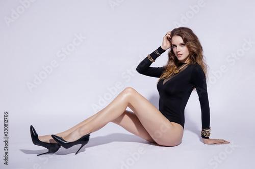 Fashion model in black bodysuit posing in studio Canvas Print