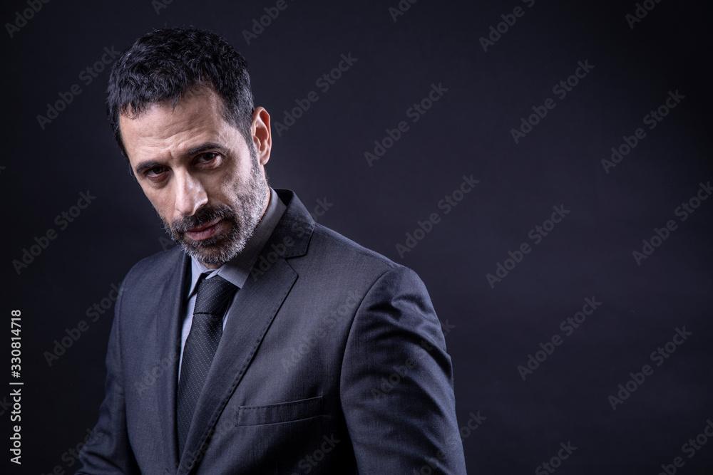 Fototapeta Ritratto di manager con barba vestito in abito e Isolato su sfondo nero