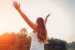 Mature middle-aged woman enjoying sunset with arms raised feeling happy in spring park. Senior woman admires landscape