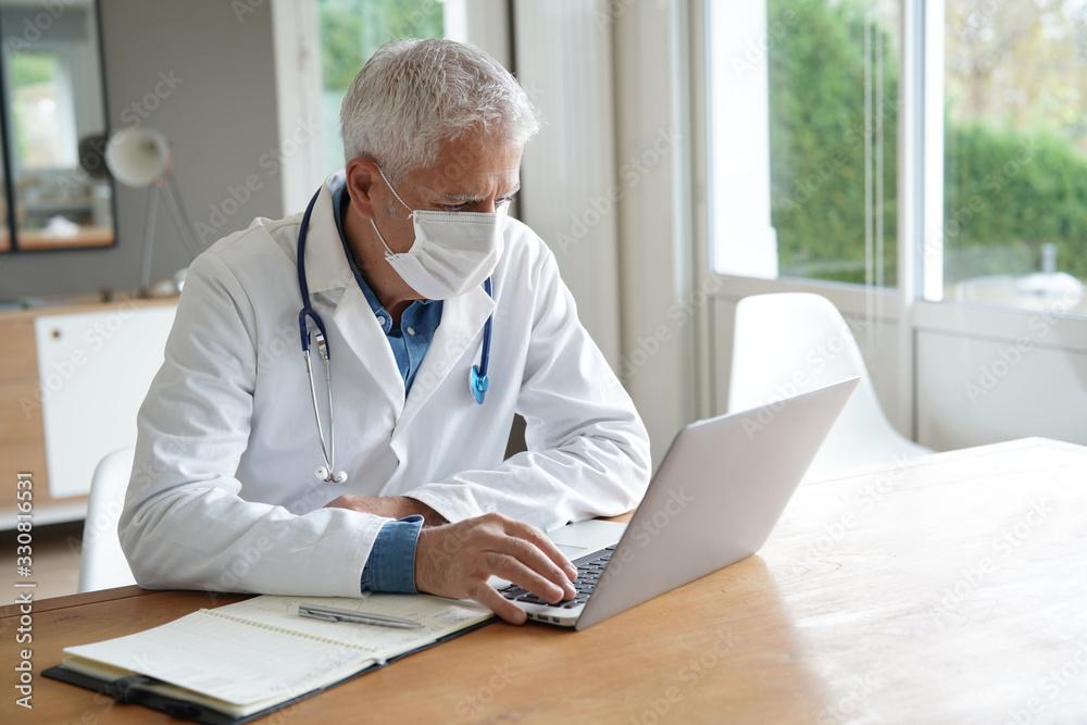 Fototapeta Doctor in office working on laptop, wearing protection mask