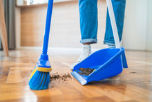 Latin Man Sweeping Wooden Floor With Broom At Home.