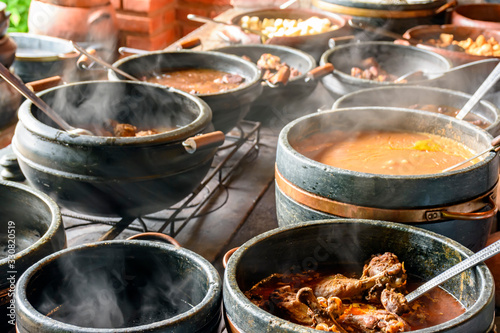 Typical Brazilian foods placed in clay pots and on a metal plate of a traditiona Wallpaper Mural