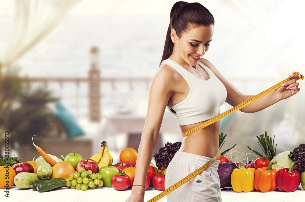 Fototapeta Beautiful fitness girl measuring her waistline with measure tape