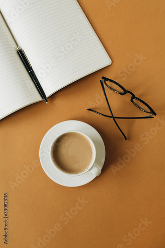 Modern home office desk workspace with notebook, cup of coffee, glasses on ginger background. Flat lay, top view work, business concept. - 330823116