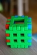canvas print picture - Vertical closeup shot of a plastic build toy cube on a wooden surface with a blurred background