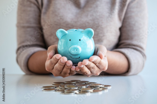 Canvas Print Young woman hands protection piggy bank and planning growing saving to strategy