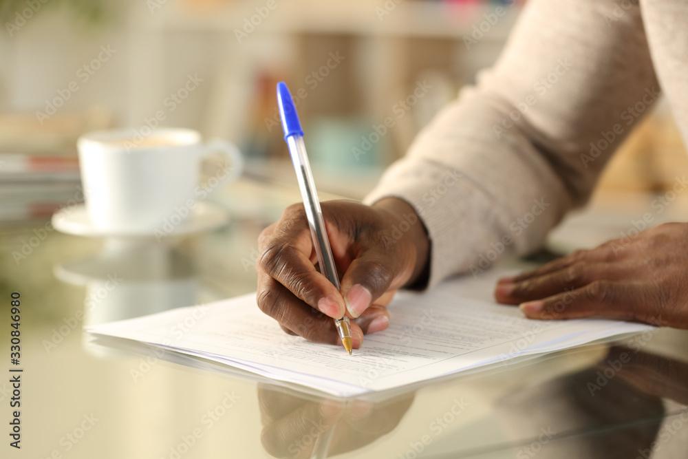 Fototapeta Black man hands filling out form on a desk