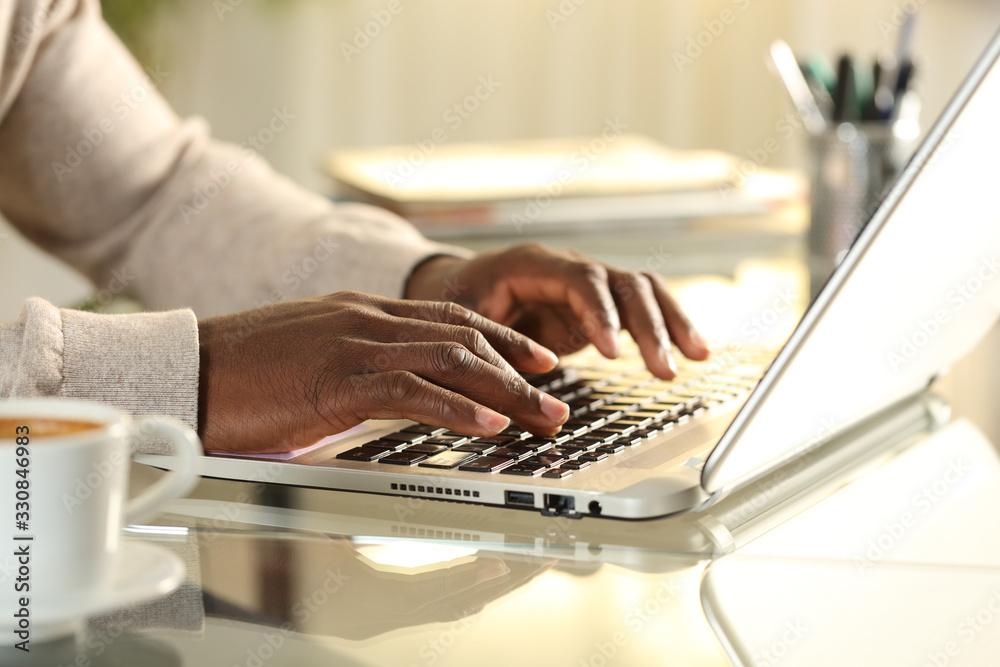 Fototapeta Black man hands typing on a laptop on a desk at home