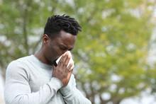 Allergic Black Man Blowing On Wipe In A Park On Spring Season