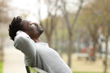 Black Man Relaxing On A Bench In A Park