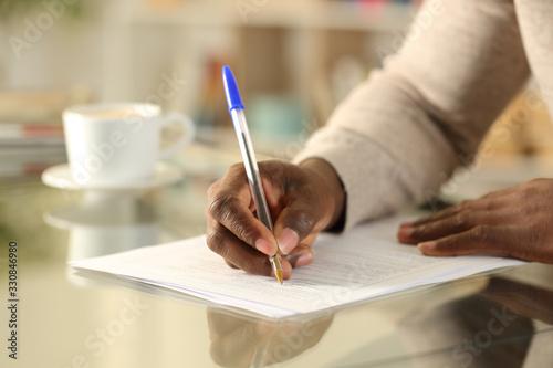Fototapeta Black man hands filling out form on a desk obraz