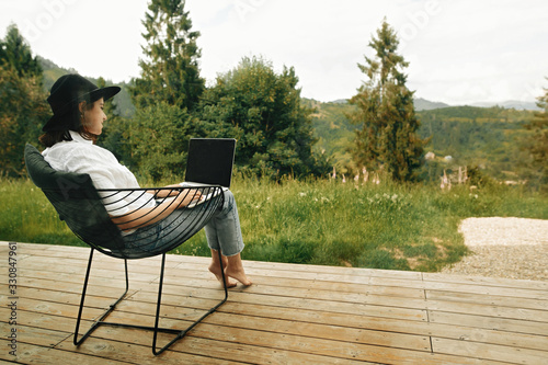 Leinwand Poster Stylish hipster girl sitting with laptop on terrace with view on woods