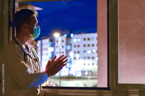 Foto Doctor with mask and stethoscope clapping out the window