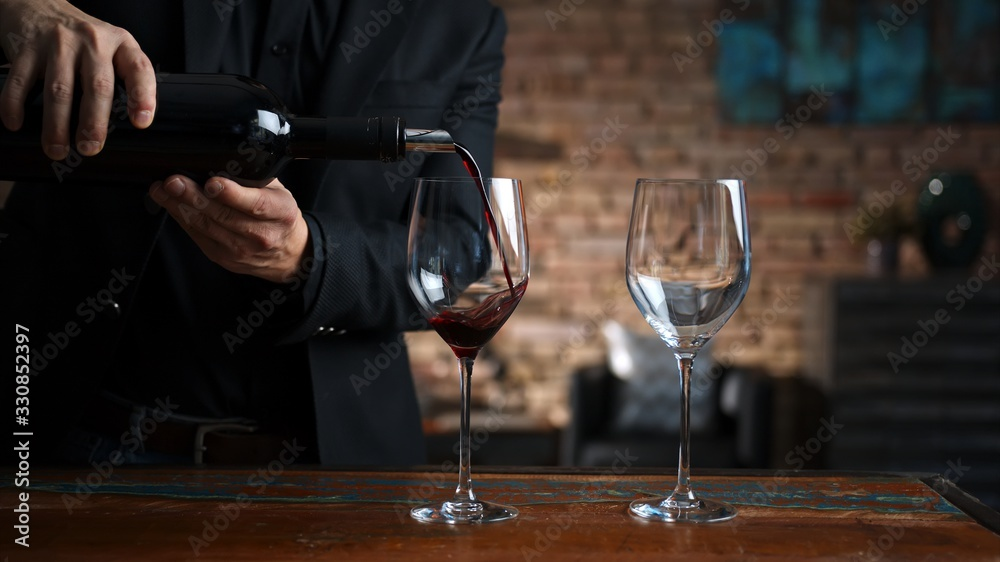 Fototapeta Man pouring red wine to wine glasses at home