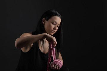 Boxing. Woman boxer sitting on bench wrapping bandage around hand close-up