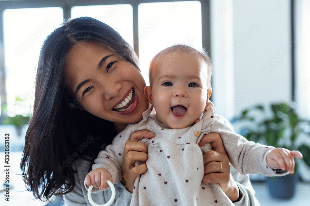 Fototapeta Happy young mother with her baby daughter looking at camera while staying at home.