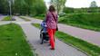 Mama z nowo narodzonym dzieckiem w wózku. Kobieta spaceruje w parku blisko lasu. Dziecko na świeżym powietrzu, dbanie o zdrowie dziecka. Noworodek śpi na spacerze. Urlop macierzyński. Słoneczny dzień.