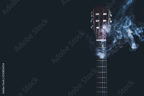 Fotografering Acoustic guitar in smoke on the black background