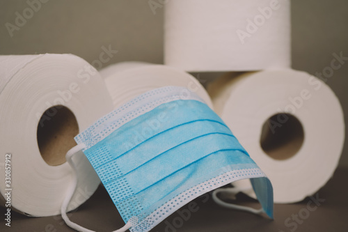 Surgical Mask Sitting In Front of Many Rolls of Toilet Paper Wallpaper Mural