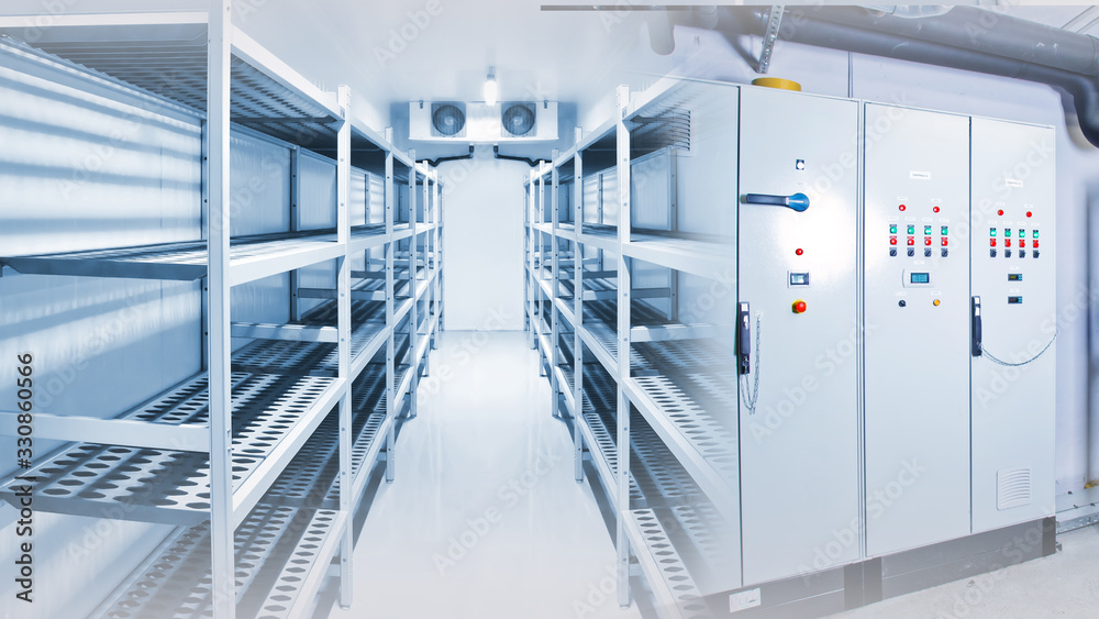 Fototapeta Refrigeration chamber for food storage. Control panels of the refrigerator. Concept - sale of freezing equipment. Equipment for food storage. Cooling. Industrial cold store with empty counters
