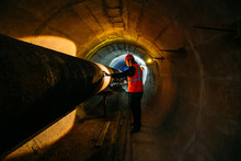Tunnel Worker Examines Pipelin...