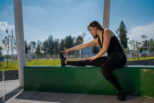 Mujer fitness con ropa oscura realiza ejercicios de estiramiento durante un día Canvas Print