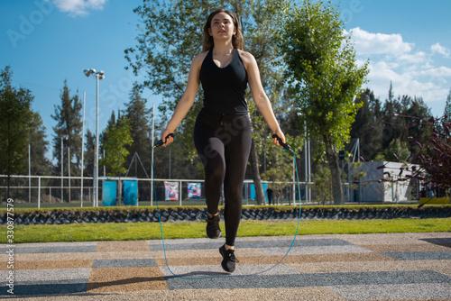 Mujer fitness con vestimenta oscura brinca la cuerda durante un día soleado Canvas Print