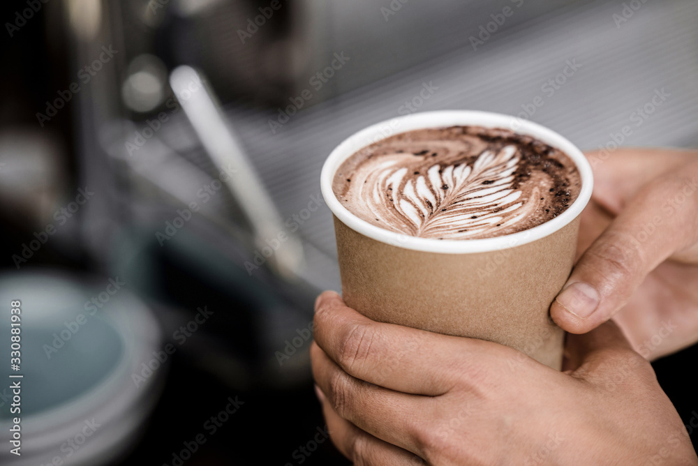 Fototapeta Close up shot of male hands holding take away cup of brewed hot coffee with Fern latte art design