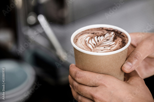 Fototapeta Close up shot of male hands holding take away cup of brewed hot coffee with Fern latte art design obraz