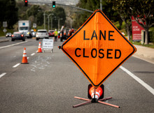 Lane Closed Orange Diamond Shaped Sign With Work Crew In Distance