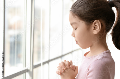 Photo Cute little Asian girl praying at home