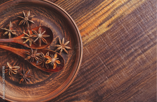 Fototapeta Anise stars in wooden spoons on a clay plate. Top view. Food concept. obraz