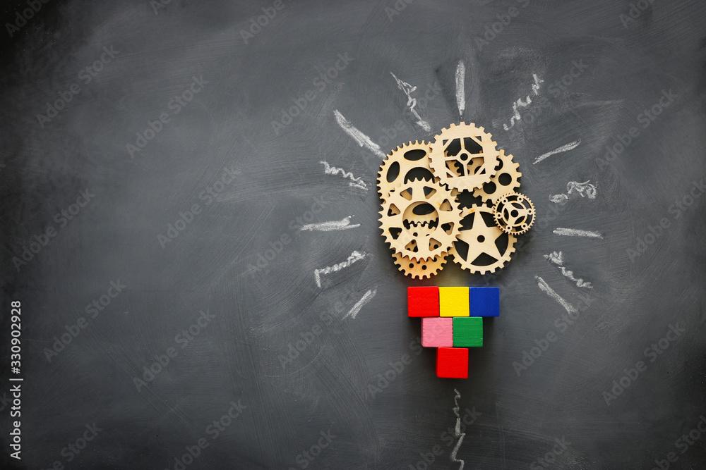 Fototapeta Education concept image. Creative idea and innovation. Wooden gears light bulb metaphor over blackboard