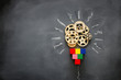 Education concept image. Creative idea and innovation. Wooden gears light bulb metaphor over blackboard